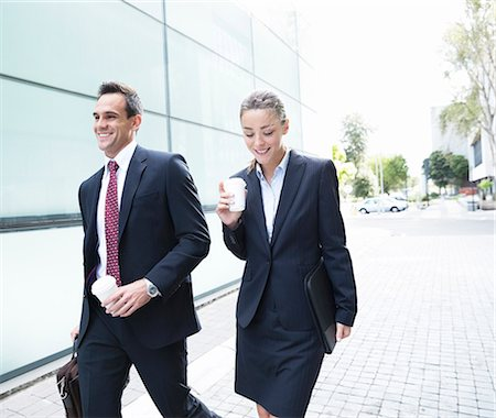 Smiling businessman and businesswoman walking with coffee Stock Photo - Premium Royalty-Free, Code: 6113-06899124