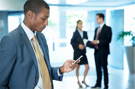 property release - Businessman text messaging with cell phone in lobby Stock Photo - Premium Royalty-Free, Code: 6113-06899130