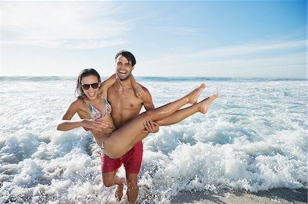 Enthusiastic man carrying woman on beach Stock Photo - Premium Royalty-Free, Code: 6113-06899265