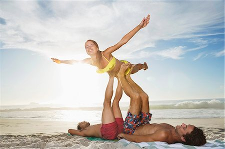 flying happy woman images - Men lifting woman with legs on beach Stock Photo - Premium Royalty-Free, Code: 6113-06899266