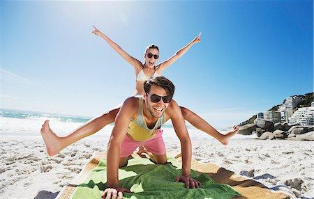 Enthusiastic couple piggybacking on beach Stock Photo - Premium Royalty-Free, Code: 6113-06899272
