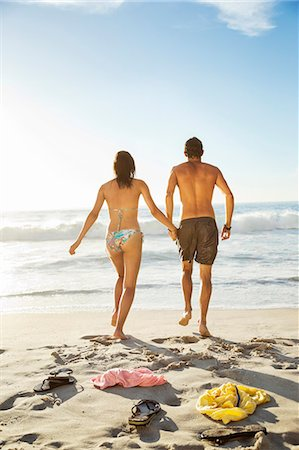 Couple holding hands and walking toward ocean on beach Stock Photo - Premium Royalty-Free, Code: 6113-06899285