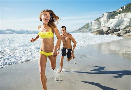 Man chasing happy woman on beach Stock Photo - Premium Royalty-Free, Code: 6113-06899290