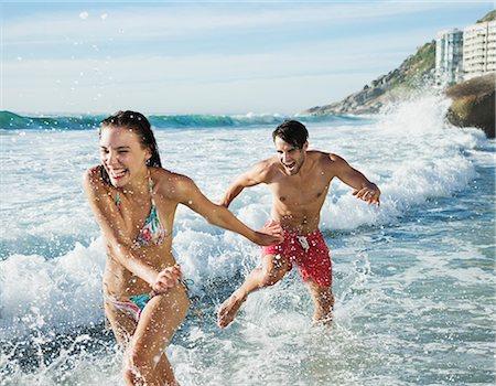 Playful couple splashing in ocean surf Stock Photo - Premium Royalty-Free, Code: 6113-06899295