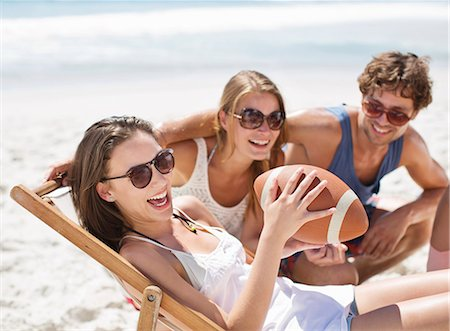 dark glasses - Smiling friends with football on beach Stock Photo - Premium Royalty-Free, Code: 6113-06899203