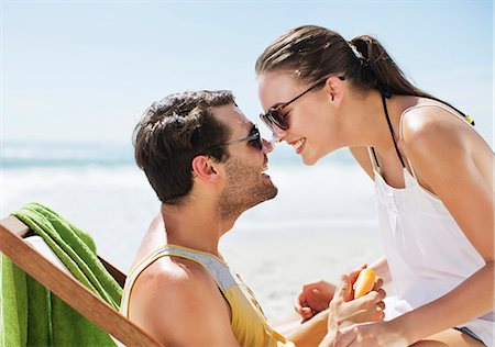 Happy couple rubbing sunscreen-covered noses on beach Stock Photo - Premium Royalty-Free, Code: 6113-06899208