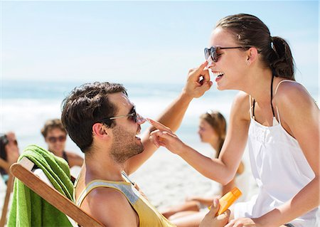 sunglasses - Couple applying sunscreen to each other's nose on beach Stock Photo - Premium Royalty-Free, Code: 6113-06899220