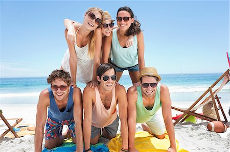 sunglasses - Portrait of happy friends forming pyramid on beach Stock Photo - Premium Royalty-Free, Code: 6113-06899238