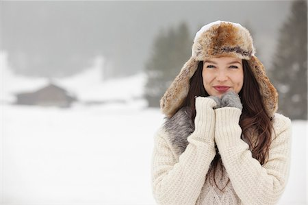 Portrait of smiling woman wearing fur hat and gloves in snowy field Stock Photo - Premium Royalty-Free, Code: 6113-06899380
