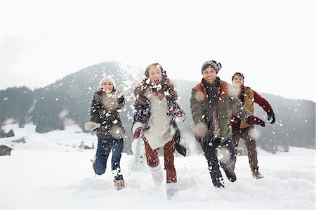 Happy friends playing in snowy field Stock Photo - Premium Royalty-Free, Code: 6113-06899313