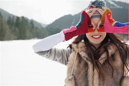 funny pose - Portrait of smiling woman circling eyes with fingers in snowy field Stock Photo - Premium Royalty-Free, Code: 6113-06899333