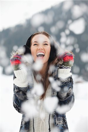 snowflakes  holiday - Enthusiastic woman enjoying falling snow Stock Photo - Premium Royalty-Free, Code: 6113-06899414