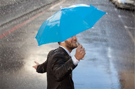 people with umbrellas in the rain - Businessman with tiny umbrella walking in rain Stock Photo - Premium Royalty-Free, Code: 6113-06899543