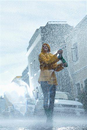 Happy woman walking barefoot in rain Stock Photo - Premium Royalty-Free, Code: 6113-06899541