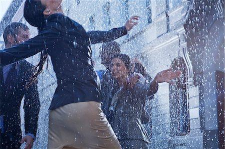 Business people dancing in rain Stock Photo - Premium Royalty-Free, Code: 6113-06899542
