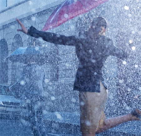 Businesswoman dancing in rain Stock Photo - Premium Royalty-Free, Code: 6113-06899549