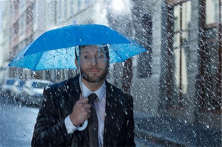 people with umbrellas in the rain - Portrait of businessman with tiny umbrella in rain Stock Photo - Premium Royalty-Free, Code: 6113-06899555