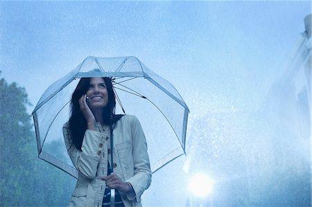 Businesswoman talking on cell phone under umbrella in rain Stock Photo - Premium Royalty-Free, Code: 6113-06899563