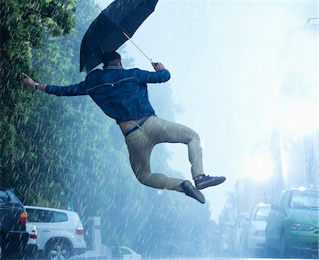 Man with umbrella jumping in rain Stock Photo - Premium Royalty-Free, Code: 6113-06899560