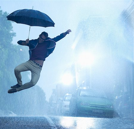 people with umbrellas in the rain - Enthusiastic man with umbrella jumping in rain Stock Photo - Premium Royalty-Free, Code: 6113-06899566