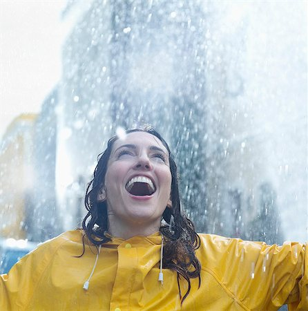 Enthusiastic woman standing in rain Stock Photo - Premium Royalty-Free, Code: 6113-06899568