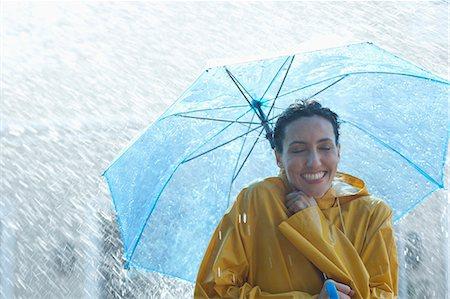 Happy woman under umbrella in rain Stock Photo - Premium Royalty-Free, Code: 6113-06899573