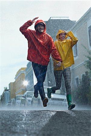 Happy couple in raincoats running down street in rain Stock Photo - Premium Royalty-Free, Code: 6113-06899572