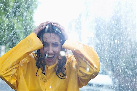 Happy woman with hands on head in rain Stock Photo - Premium Royalty-Free, Code: 6113-06899577