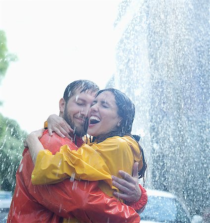 Happy couple hugging in rain Stock Photo - Premium Royalty-Free, Code: 6113-06899575
