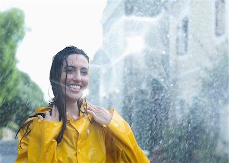 Enthusiastic woman standing in rain Stock Photo - Premium Royalty-Free, Code: 6113-06899580