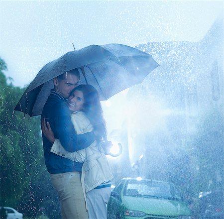 partnership - Happy couple hugging under umbrella in rain Stock Photo - Premium Royalty-Free, Code: 6113-06899581