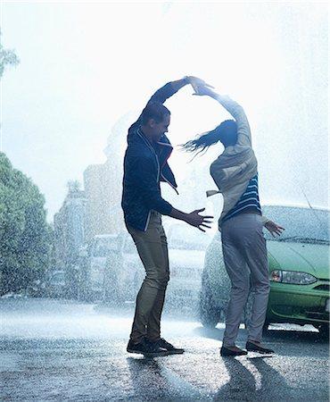 Happy couple dancing in rain Stock Photo - Premium Royalty-Free, Code: 6113-06899584