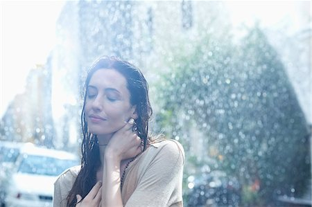 Serene woman standing in rain Stock Photo - Premium Royalty-Free, Code: 6113-06899585