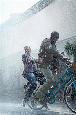 Happy couple riding bicycle in rainy street Stock Photo - Premium Royalty-Free, Code: 6113-06899589