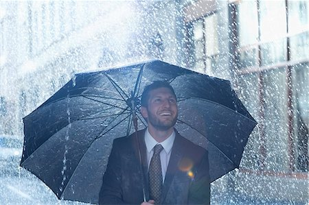 people with umbrellas in the rain - Happy businessman under umbrella in rain Stock Photo - Premium Royalty-Free, Code: 6113-06899590