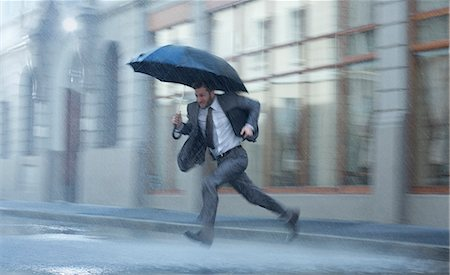 people with umbrellas in the rain - Businessman with umbrella running across rainy street Stock Photo - Premium Royalty-Free, Code: 6113-06899595
