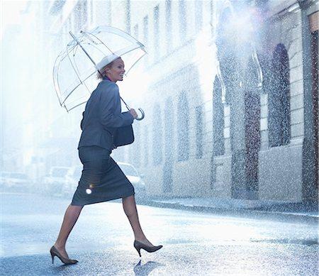 Happy businesswoman with umbrella walking across rainy street Stock Photo - Premium Royalty-Free, Code: 6113-06899596