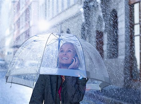 people with umbrellas in the rain - Smiling businesswoman talking on cell phone under umbrella in rainy street Stock Photo - Premium Royalty-Free, Code: 6113-06899599