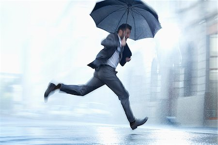 Businessman running with umbrella in rainy street Stock Photo - Premium Royalty-Free, Code: 6113-06899524