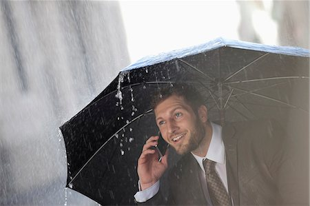 people with umbrellas in the rain - Businessman talking on cell phone under umbrella in rain Stock Photo - Premium Royalty-Free, Code: 6113-06899529
