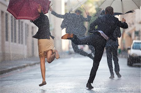people with umbrellas in the rain - Business people with umbrellas dancing in rain Stock Photo - Premium Royalty-Free, Code: 6113-06899533