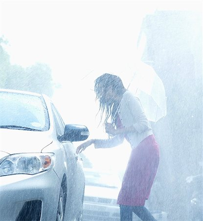people with umbrellas in the rain - Woman with umbrella reaching for car door handle in rain Stock Photo - Premium Royalty-Free, Code: 6113-06899534