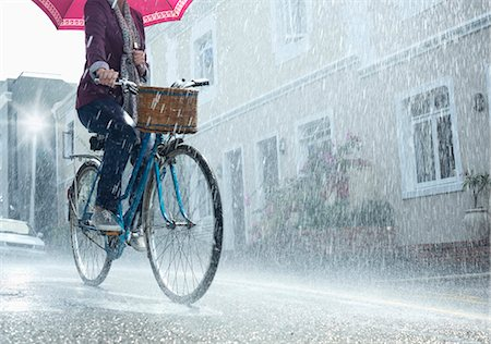 people with umbrellas in the rain - Woman riding bicycle with umbrella in rainy street Stock Photo - Premium Royalty-Free, Code: 6113-06899535