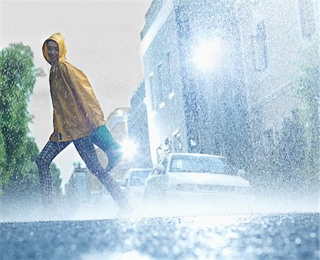 Woman walking barefoot on rainy street Stock Photo - Premium Royalty-Free, Code: 6113-06899539