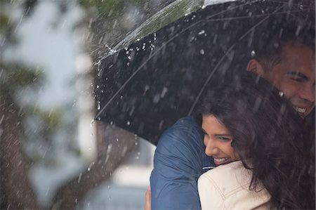 people with umbrellas in the rain - Happy couple hugging under umbrella in rain Stock Photo - Premium Royalty-Free, Code: 6113-06899644