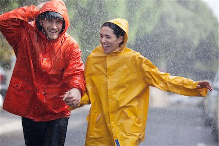 safety - Happy couple holding hands and running in rainy street Stock Photo - Premium Royalty-Free, Code: 6113-06899653