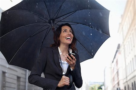 people with umbrellas in the rain - Happy businesswoman text messaging with cell phone under umbrella in rain Stock Photo - Premium Royalty-Free, Code: 6113-06899663