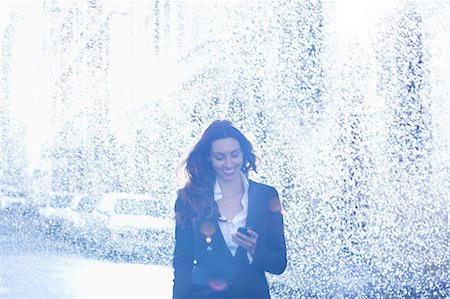 Happy businesswoman text messaging with cell phone in rain Stock Photo - Premium Royalty-Free, Code: 6113-06899662