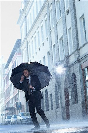 people with umbrellas in the rain - Businessman talking on cell phone under umbrella in rainy street Stock Photo - Premium Royalty-Free, Code: 6113-06899668
