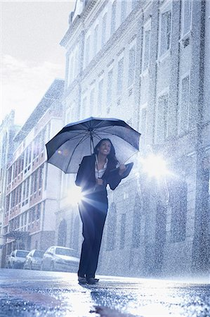 people with umbrellas in the rain - Businesswoman standing under umbrella in rainy street Stock Photo - Premium Royalty-Free, Code: 6113-06899669